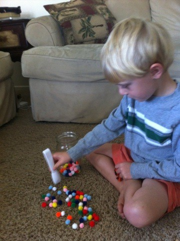 Elementary school child teaches his brother a game to improve fine motor skills.
