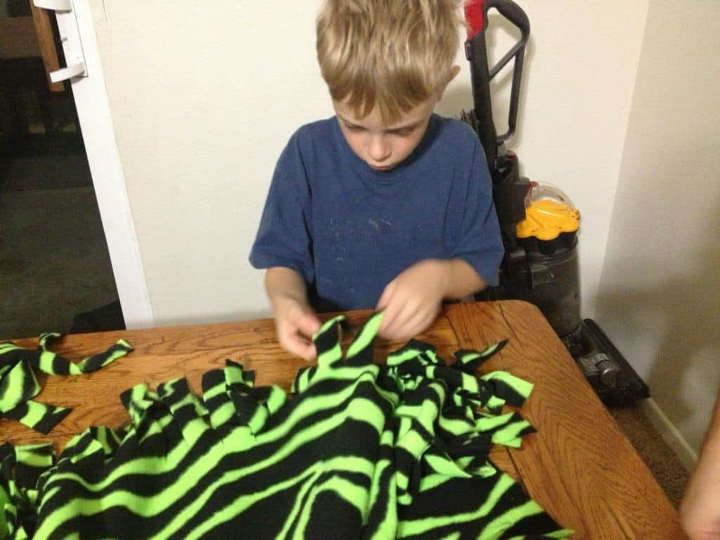 Child ties a no-sew fringe blanket