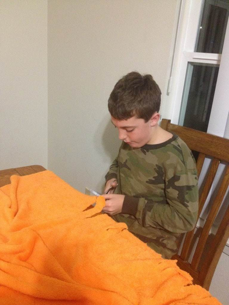 Jonathan (age 11) cuts his minkee fringe blanket