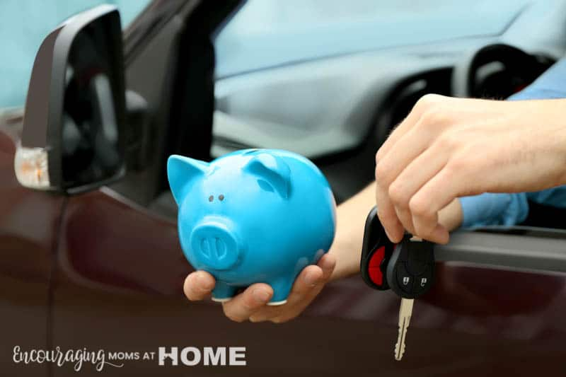 Man holding piggy bank and key in his new car